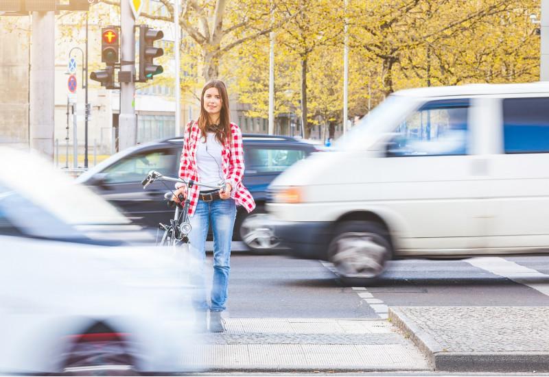 eine junge Frau wartet, ein Fahrrad schiebend, auf einer Mittelinsel an einer roten Ampel, vor und hinter ihr fahren Autos vorbei