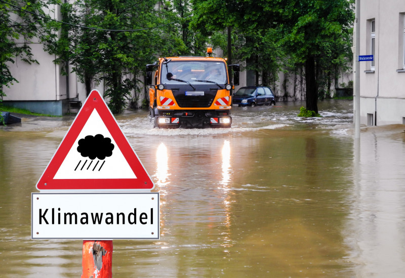 """überflutete Straße in der Stadt, davor ein Warnschild """"Regen / Klimawandel"""", ein kommunales Einsatzfahrzeug bahnt sich den Weg durchs Wasser"""