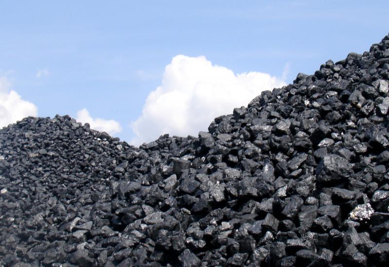 schwarze Kohlenstücke liegen zu einem Haufen aufgetürmt im Freuen, dahinter ist blauer Himmel mit weißen Wolken zu sehen