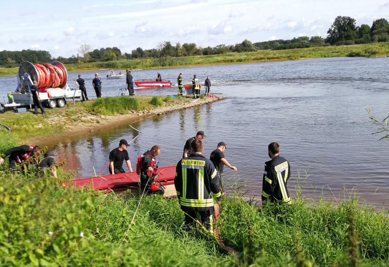 Feuerwehrleute mit Booten an und auf einem Fluss im Einsatz