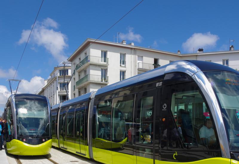 Menschen an einer Haltestelle steigen in eine moderne Straßenbahn in der Stadt