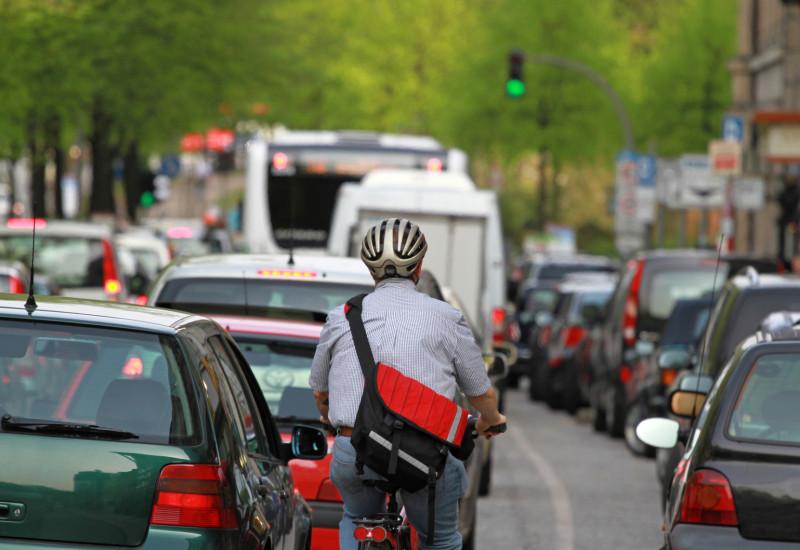 Fahrradfahrer auf einer zugestauten Stadtstraße