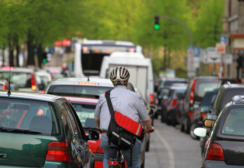 Radfahrer zwischen Autos im Stau