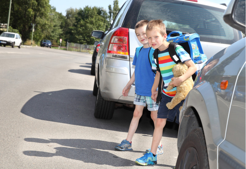 zwei Schulkinder überqueren zwischen parkenden Autos eine Straße