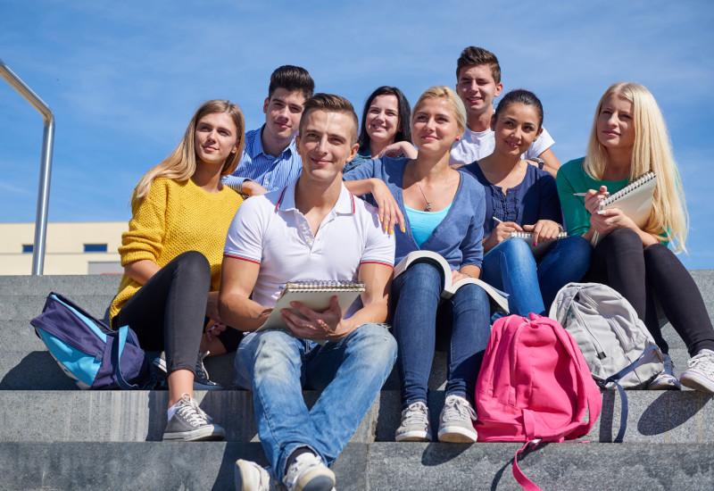 eine Gruppe Studentinnen und Studenten sitzt mit Rucksäcken und Schreibblöcken auf einer Steintreppe