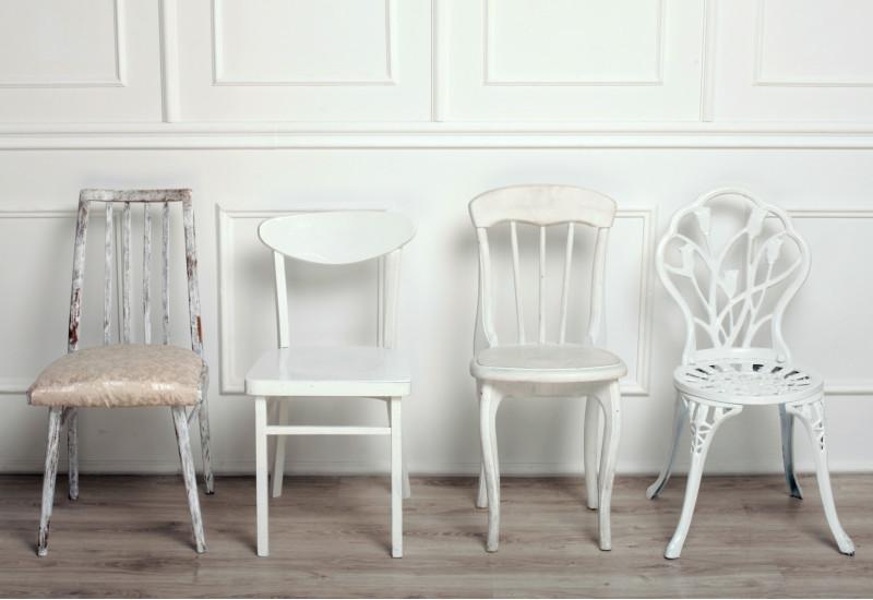 drei weiße Stühle im unterschiedlichen Stil vor einer weiß vertäfelten Wand mit Holzdielenboden