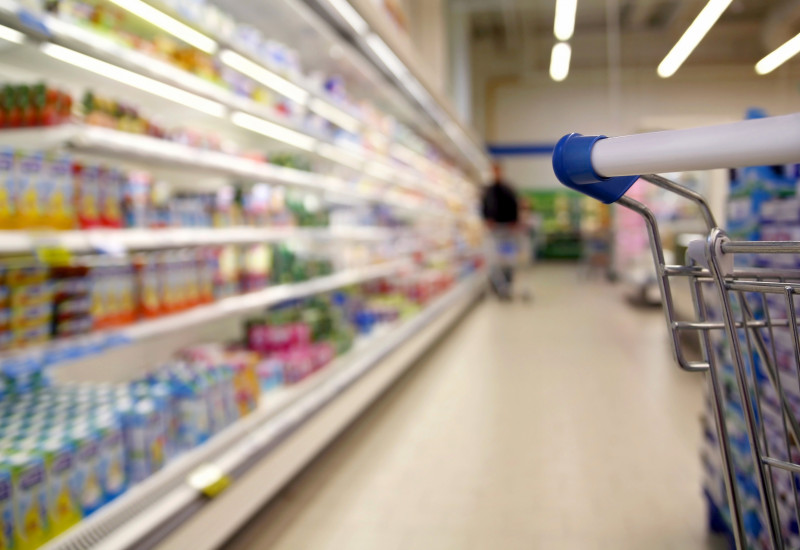 ein Gang in einem Supermarkt entlang eines Kühlregals