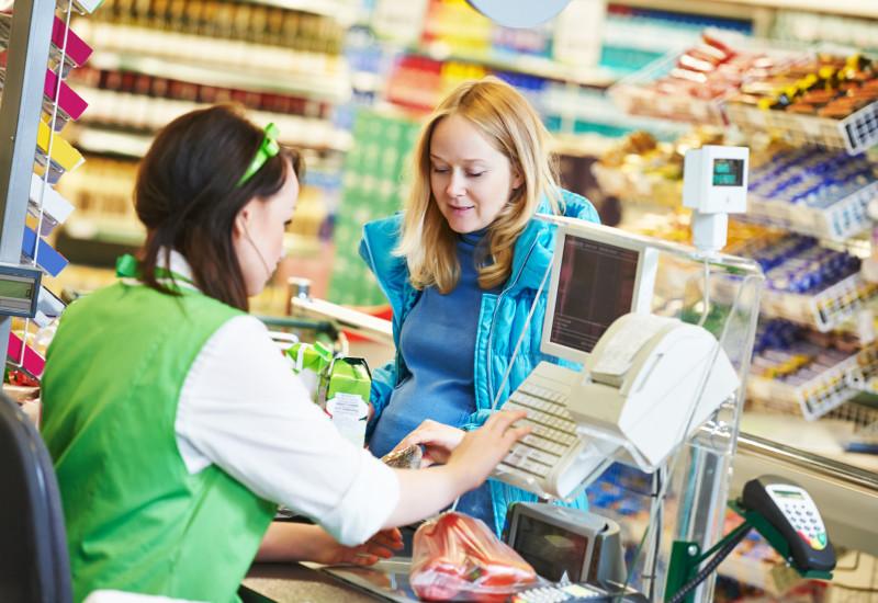 eine Frau bezahlt in einem Supermarkt ihren Einkauf bei der Kassiererin