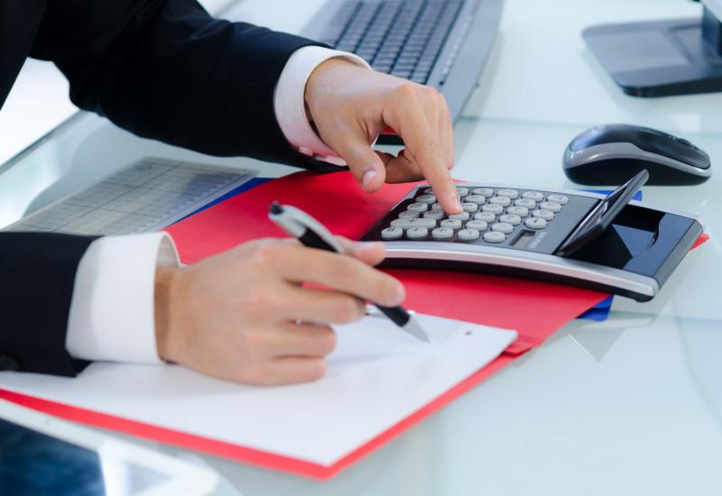 ein Mann im Anzug und weißen Hemd sitzt an einem Schreibtisch und rechnet mit einem Taschenrechner