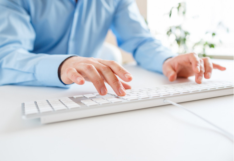 Mann tippt auf einer Tastatur