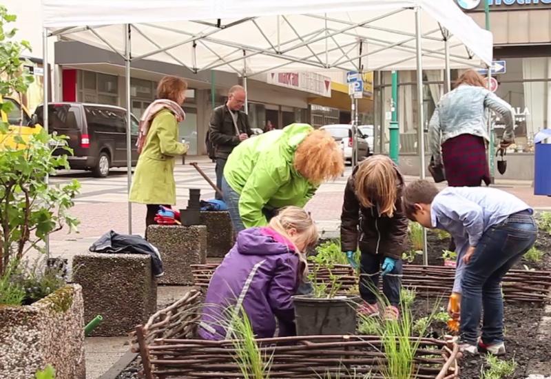 Erwachsene und Kinder bei einer Urban-Gardening-Aktion