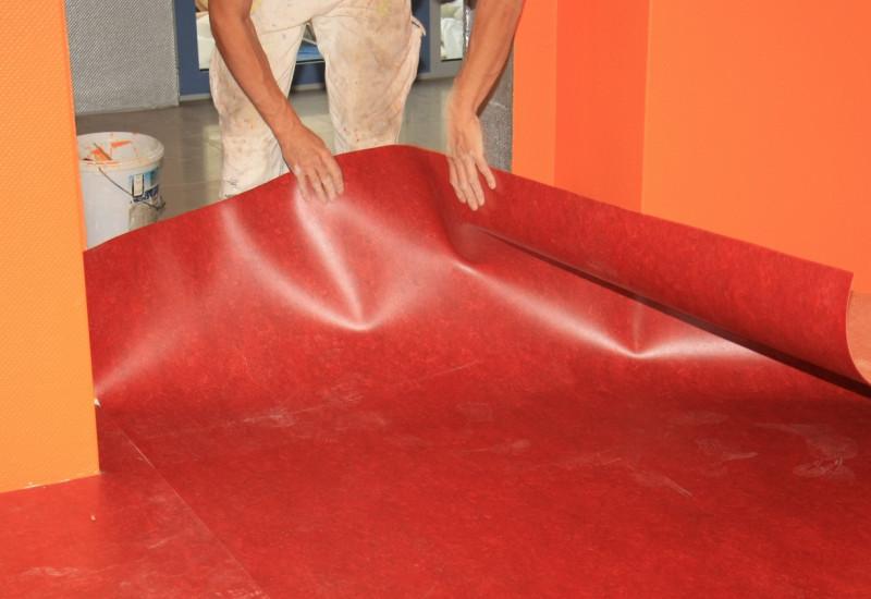 Handwerker verlegt in einer frisch gestrichenen Wohnung einen Fußbodenbelag