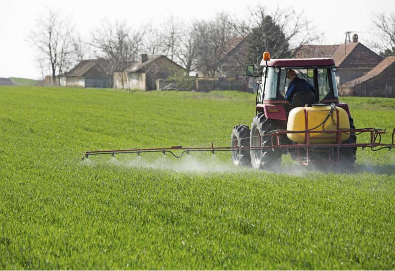 ein Traktor spritzt Pestizide auf einem Feld