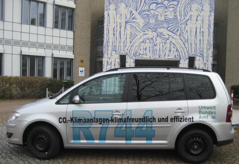 """silbergraues Auto mit der Aufschrift """"CO2-Klimaanlagen - klimafreundlich und effizient, R744"""" und dem Logo des Umweltbundesamtes"""