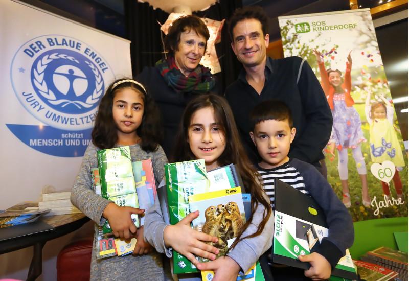 Gruppenfoto: Maria Krautzberger, Oliver Mommsen und drei Kinder mit Kinderheften, Taschentücher-Paketen und anderen Produkten im Arm