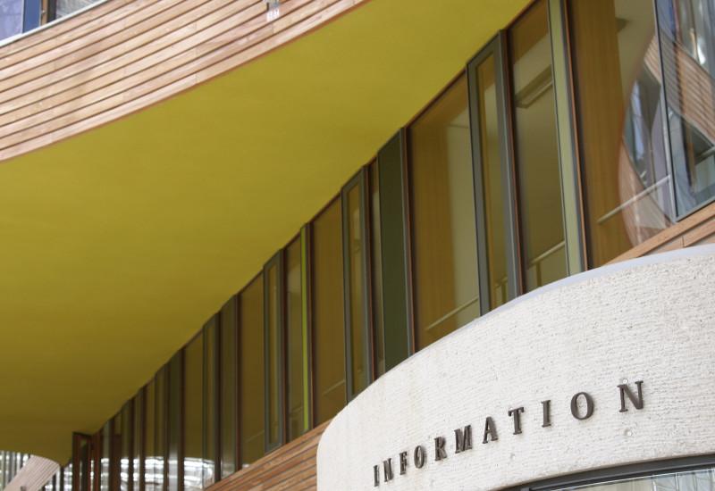 """Foto im Innenhof: Moderne Innenfassade mit Glasscheiben, farbigen Flächen und Holz sowie Pförtnerloge mit der Aufschrift """"Information"""""""