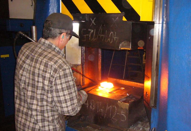 Mann arbeitet an einem glühenden Metallteil in einer Schmiedemaschine