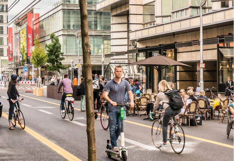 Fußgängerzone mit Radspur, Tischen vor Cafés, Geschäften und Bäumen in Kübeln mit Sitzgelegenheiten