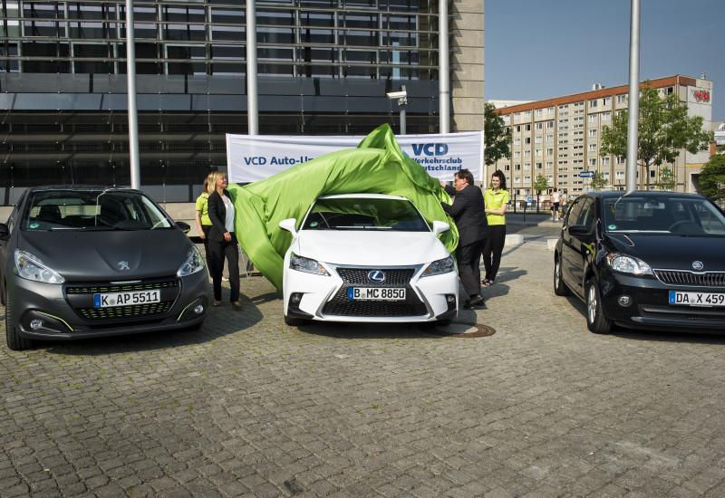 drei Autos stehen auf einem gepflasterten Platz, eine Frau und ein Mann ziehen ein grünes Tuch vom mittleren Auto, um es zu enthüllen. Im Hintergrund steht ein Banner des Verkehrsclubs Deutschland