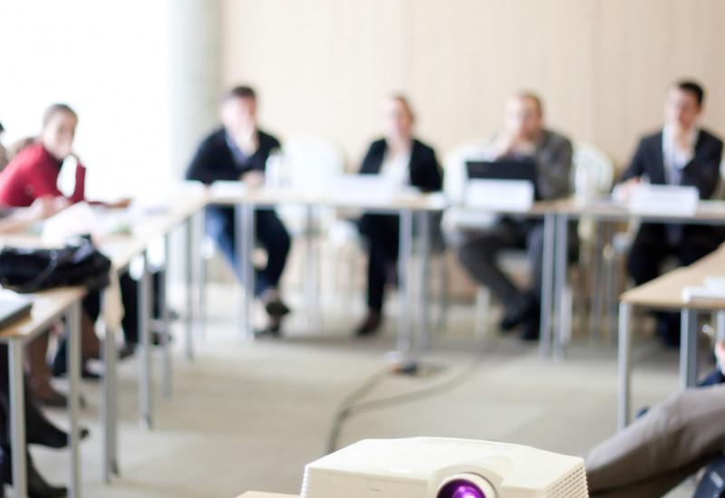 etwa 10 Leute sitzen auf einer Veranstaltung an U-förmig aufgestellten Tischen mit Namensschildern und Laptops, vorne läuft ein Beamer
