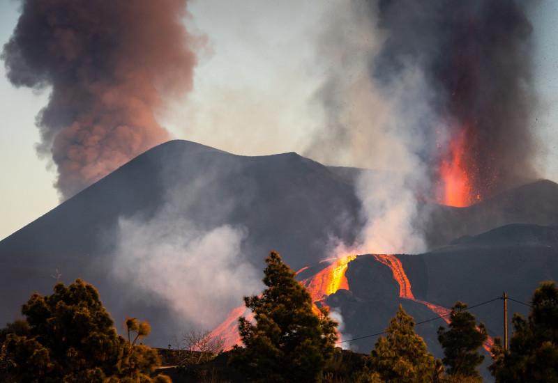 aus einem Vulkan steigen Rauchwolken auf und es fließt glühende Lava hinab