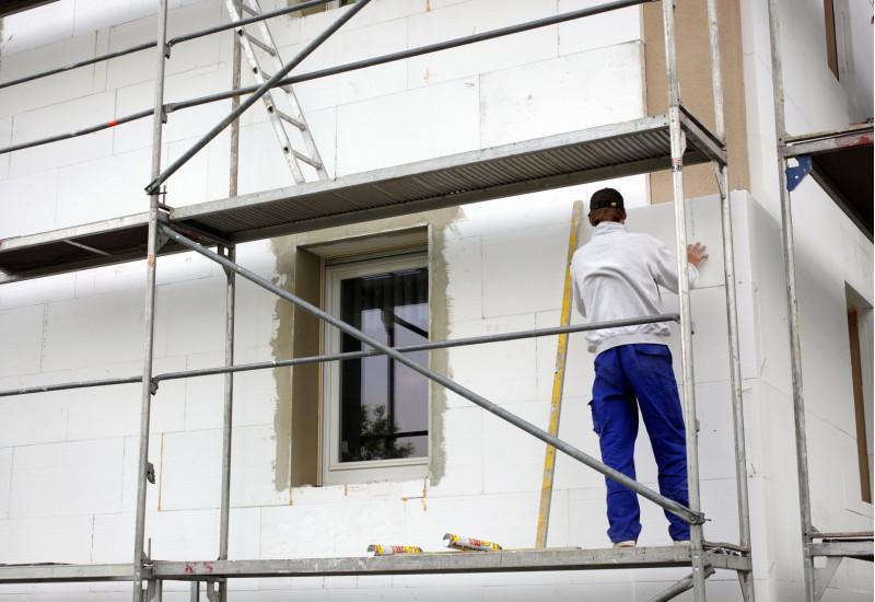 Handwerker steht auf einem Baugerüst und bringt Styroporplatten an eine Hausfassade an