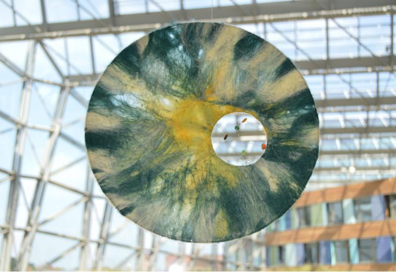 an einer Glasfront des UBA Dessau hängt eine halbtransparente Scheibe, die an Sonne, Mond, Himmel und Wolken erinnert. Ein Guckloch bietet einen Einblick ins Innere des Gebäudes