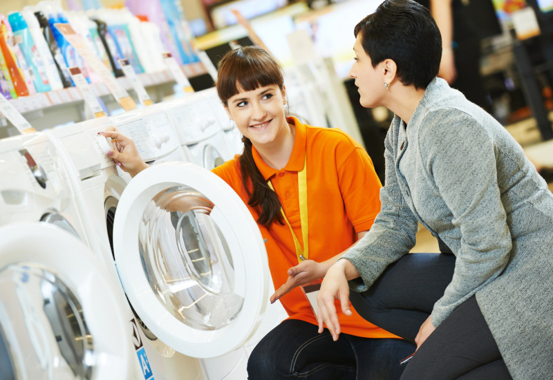 eine Verkäuferin berät eine Kundin zu einer Waschmaschine