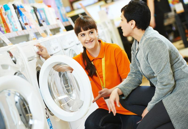 Eine Verkäuferin zeigt einer Kundin Waschmaschinen