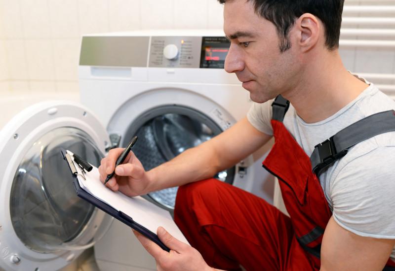 Monteur macht sich Notizen zu einer defekten Waschmaschine