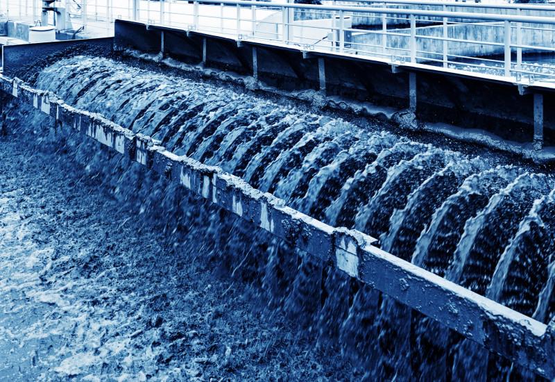 in einer Kläranlage: schlammiges Wasser fließt eine Art Wehr hinunter
