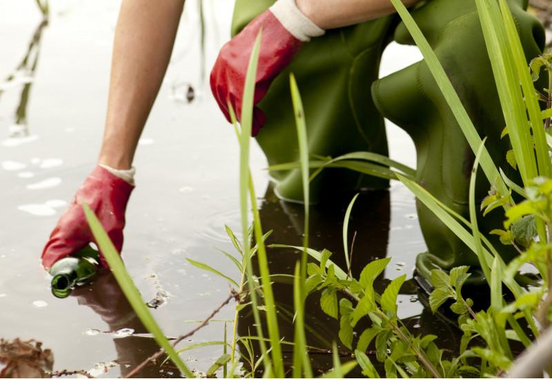 ein Mensch in einer grünen Wathose und mit Gummihandschuhen steht in einem See und nimmt eine Wasserprobe