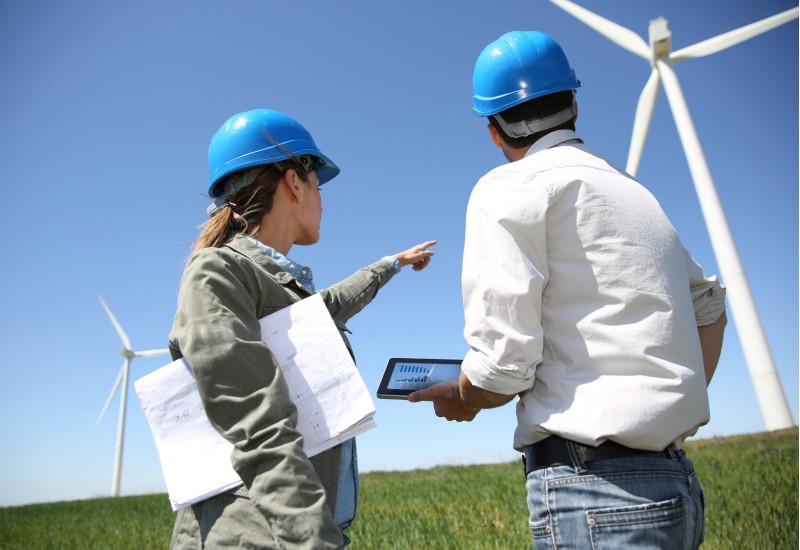 eine Frau und ein Mann mit blauen Bau-Schutzhelmen stehen mit einem Tablet und Papierunterlagen in der Hand auf einer Wiese und zeigen auf eine Windkraftanlage