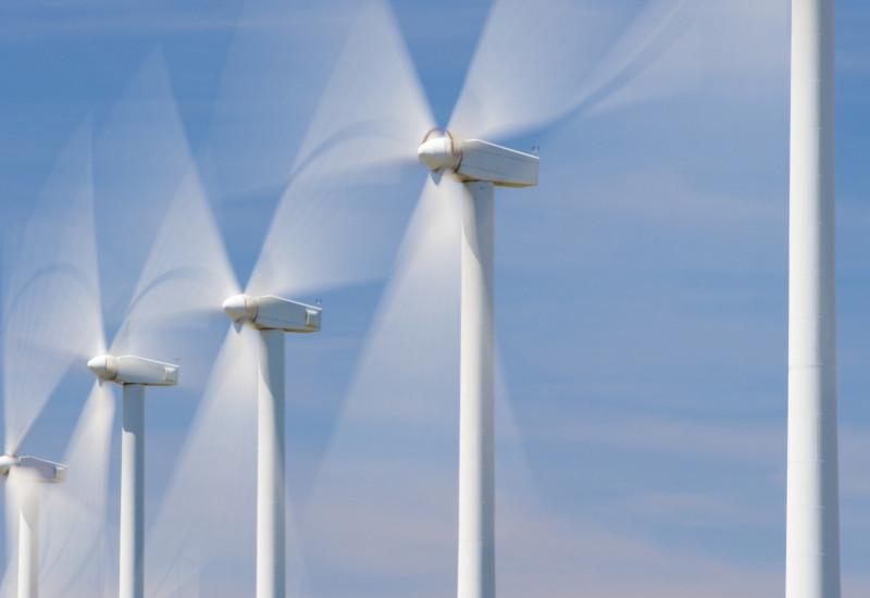 Windkraftanlagen drehen sich vor blauem Himmel