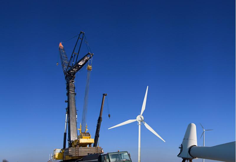 Kran und Windkraftanlagen, zum Teil in Einzelteilen