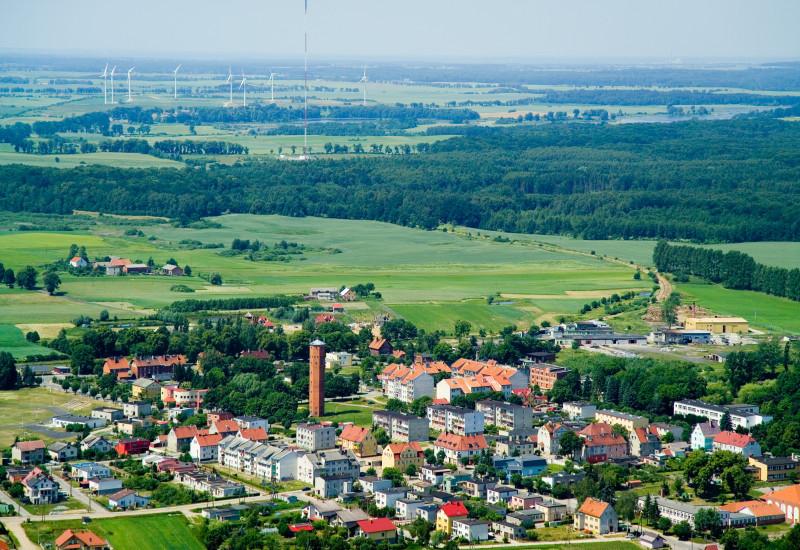 Kleinstadt, in der Ferne sind Windkraftanlagen zu sehen