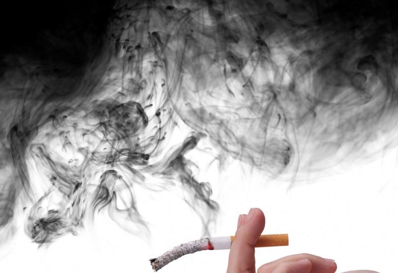 Hand hält eine schon halb zu Asche gewordene Zigarette, von der schwarzer Qualm aufsteigt