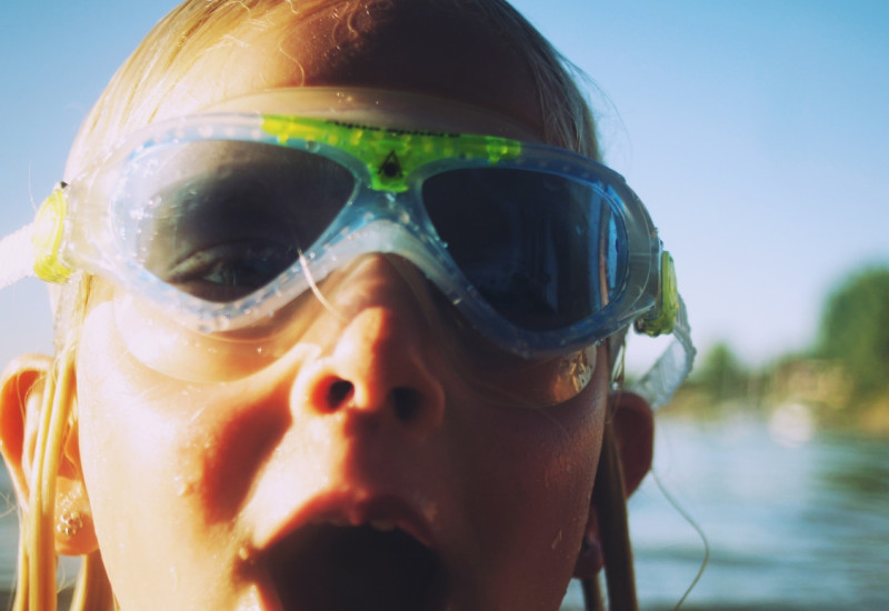 Ein Mädchen schwimmt im offenen Wasser: Sie trägt eine Schwimmbrille.