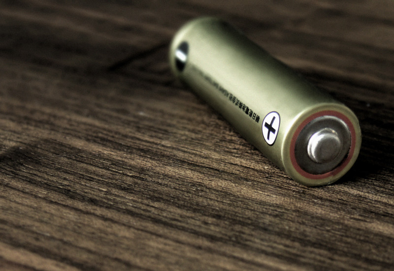 Eine einzelne Batterie liegt auf einem Holztisch