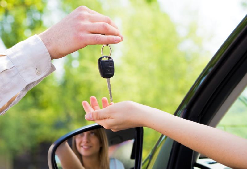 Eine Frau sitzt im Auto, von außen erhält sie von einem Mann durch das Fenster den Autoschlüssel