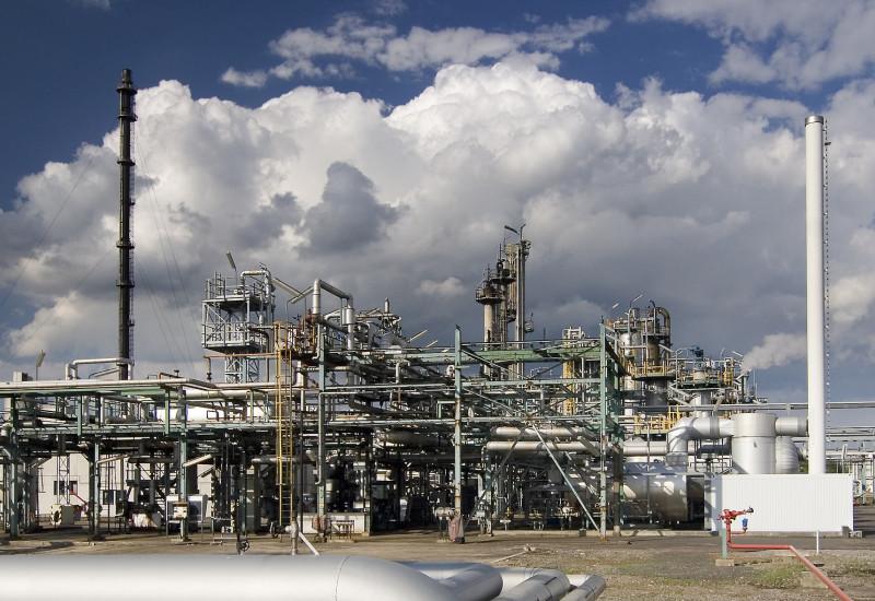 Nahaufnahme einer Chemieanlage vor wolkigem Himmel