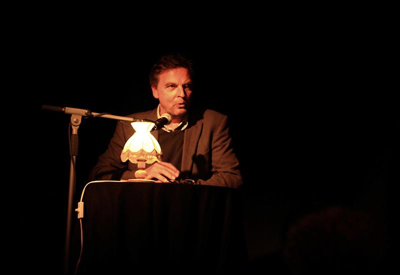 Ein Mann liest auf einer Bühne aus einem Buch
