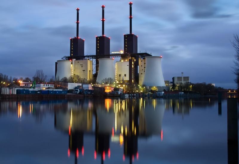 Energiekraftwerk bei Nacht, die Beleuchtung der hohen Schornsteine spiegelt sich im Wasser.