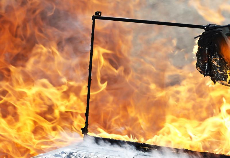 Ein brennender Laptop, im Hintergrund Feuer