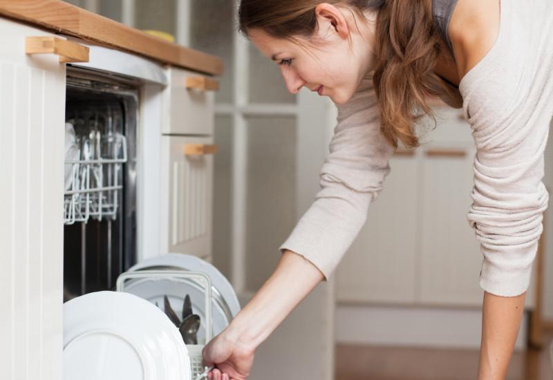 Eine Frau räumt die Spülmaschine ihrer Einbauküche ein