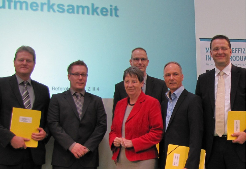 Bundesumweltministerin Hendricks und fünf Herren in Anzügen stehen lächelnd auf einer Bühne, drei Herren haben gelbe Mappen unter dem Arm, im Hintergrund ein Plakat zum Umweltinnovationsprogramm