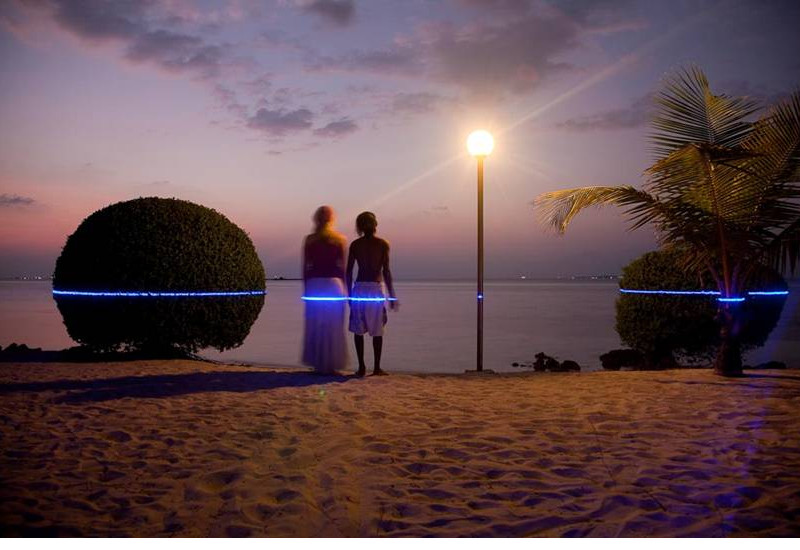 Ein Pärchen steht am Strand blickt in den Sonnenuntergang über dem Meer. In Hüfthöhe zeigt ein blauer Laser, wie hoch Ihnen das Wasser stehen könnte.