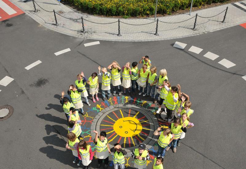 Kinder stehen jubelnd um einen Gullideckel, den sie bunt mit einer Sonne bemalt haben