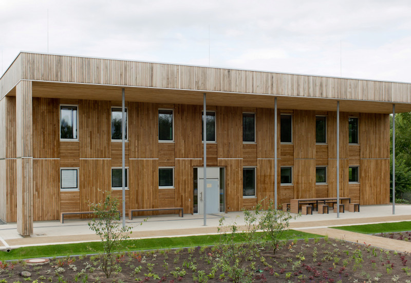 zweistöckiges, quadratisches Haus mit Flachdach und Holzfassade, davor sind Außenanlagen frisch bepflanzt und Wege neu angelegt