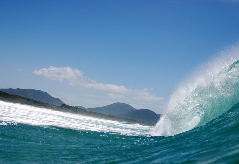 Aufnahme einer Welle, im Hintergrund eine Insel